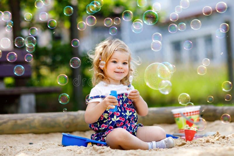 Belle petite fille blonde d'enfant en bas âge ayant l'amusement avec le ventilateur de soufflement de bulle de savon Enfant adora image libre de droits
