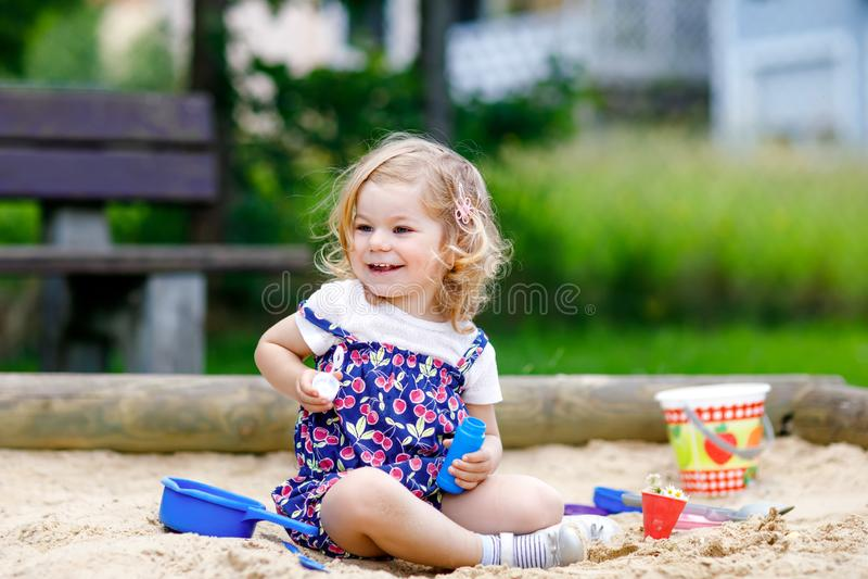 Belle petite fille blonde d'enfant en bas âge ayant l'amusement avec le ventilateur de soufflement de bulle de savon Enfant adora images libres de droits