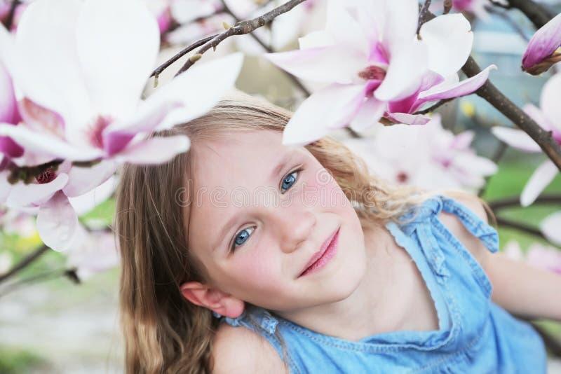 Belle petite fille blonde dans la robe bleue tenant des fleurs de magnolia sous l'arbre de magnolia de fleur images stock