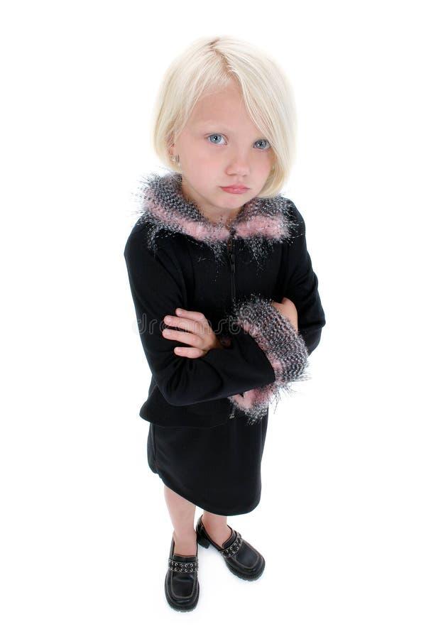 Belle petite fille boudante dans le procès noir avec les clavettes roses photographie stock libre de droits