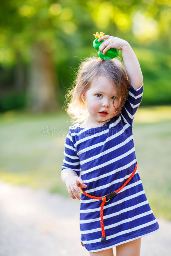 Belle petite fille dans des bottes de pluie rouges jouant avec la grenouille en caoutchouc photos libres de droits