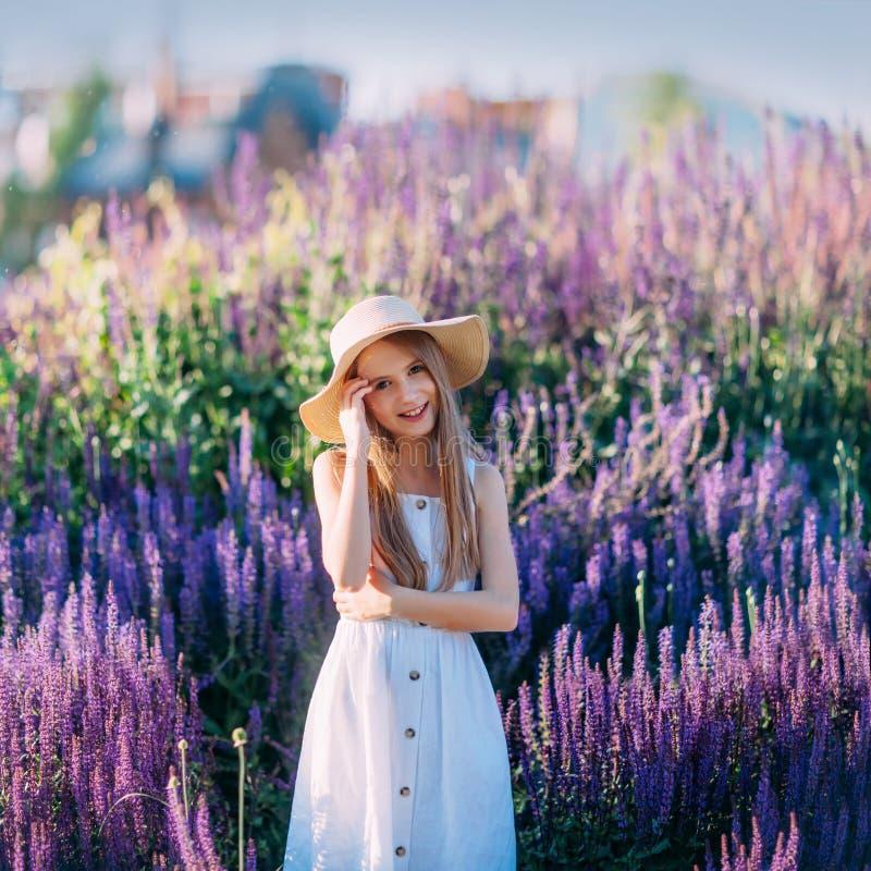 Belle petite fille dans le chapeau et la robe blancs souriant en parc photos stock