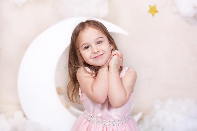 Belle petite fille dans le studio sur un fond de la lune, des étoiles et des nuages La petite fille r?ve R?ves doux mignon photographie stock