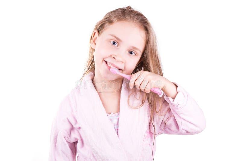 Belle petite fille de sourire heureuse se brossant les dents après bain, douche photo libre de droits