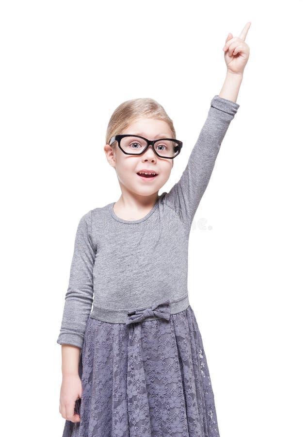 Belle petite fille en verres montrant sur quelque chose par le doigt photo stock