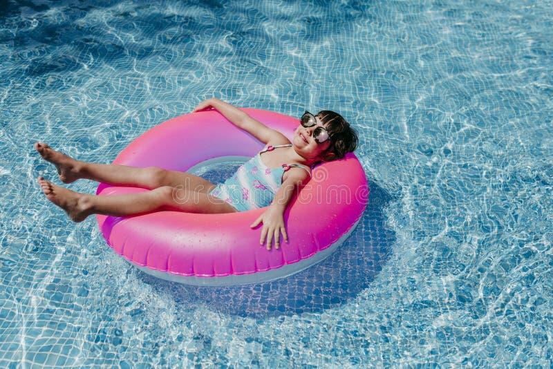 belle petite fille flottant sur des beignets roses dans un bassin Porter des lunettes de soleil et sourire Amusement et mode de v photo stock