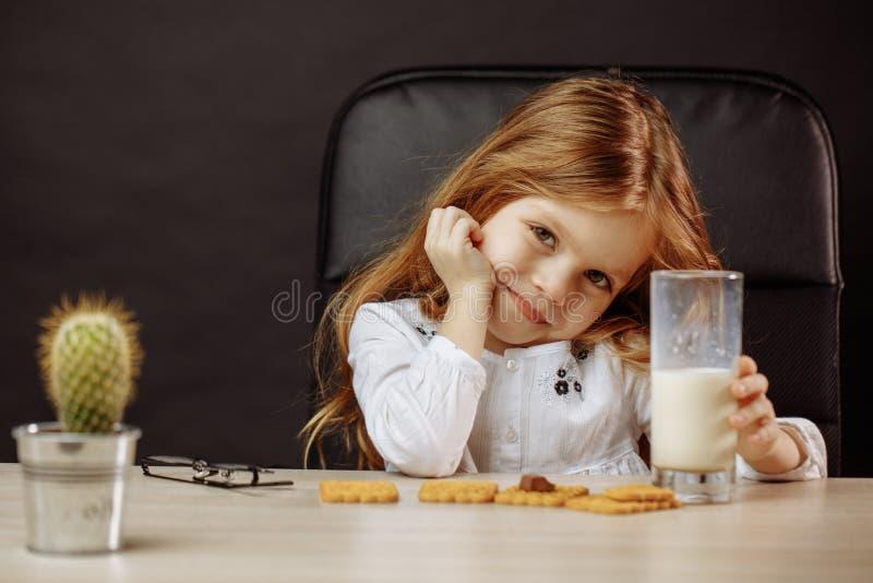 Belle petite fille heureuse ayant un casse-croûte avec du lait et des biscuits images stock