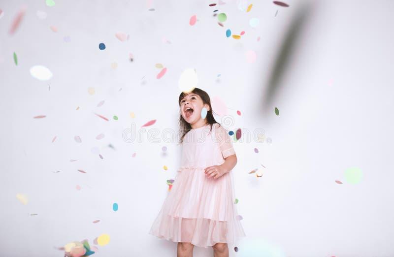 Belle petite fille heureuse portant la robe rose avec la couronne de princesse appréciant la surprise colorée de confettis tomban photo libre de droits
