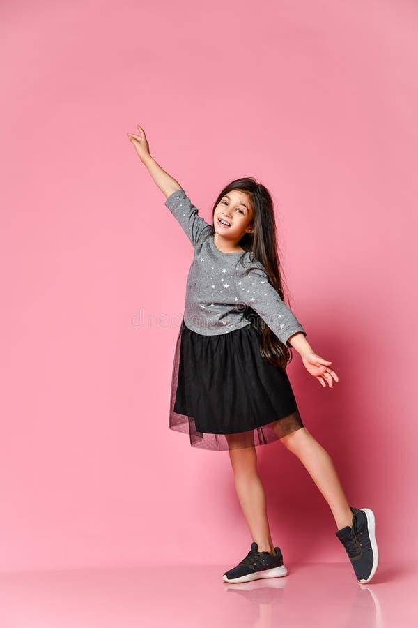 Belle petite fille intégrale avec long dans la robe grise et des espadrilles se tenant et posant sur un fond rose photo stock