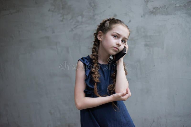 Belle petite fille invitant le téléphone portable image stock
