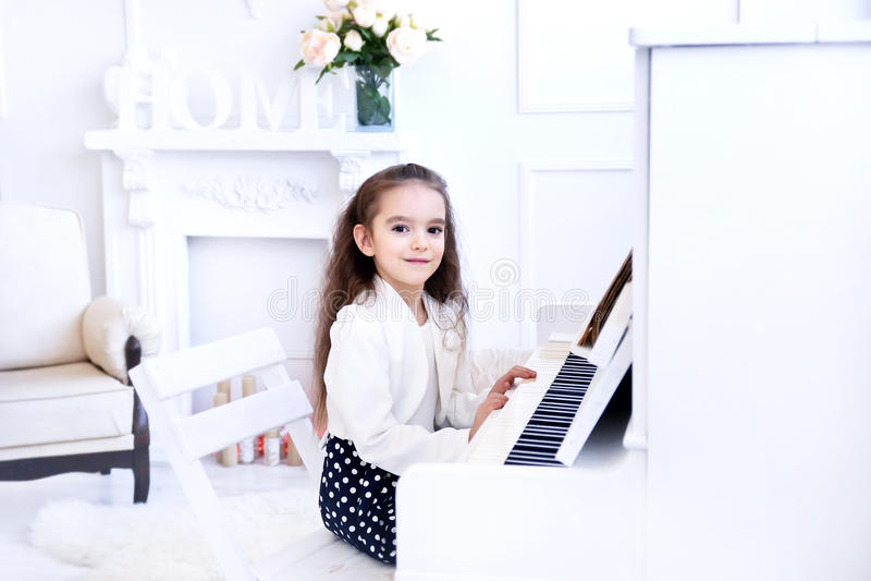 Belle petite fille jouant le piano dans le salon blanc image libre de droits