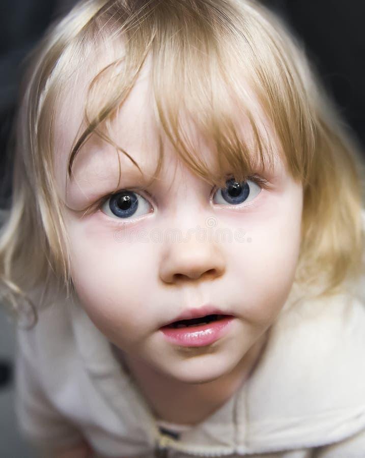 Belle petite fille la blonde avec les yeux bleus énormes recherchant photo stock