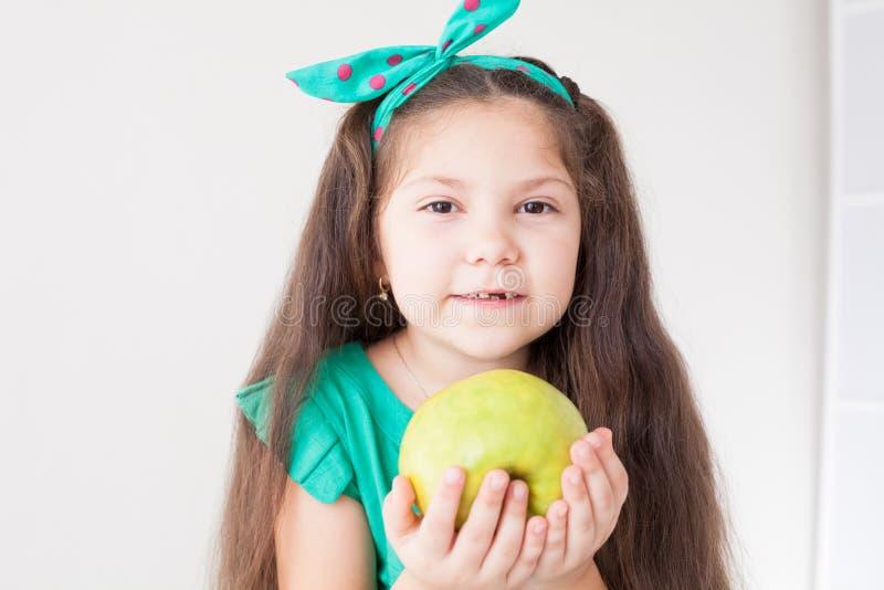 Belle petite fille mangeant d'un fruit vert d'Apple photo libre de droits
