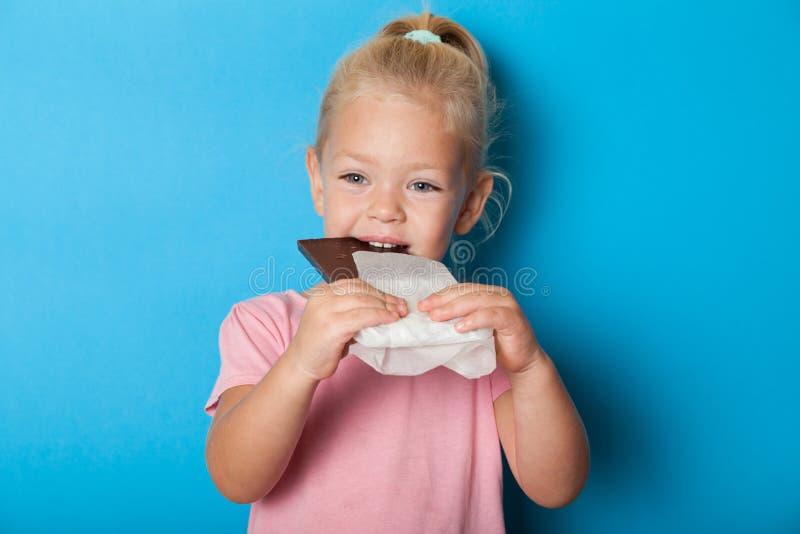 Belle petite fille mangeant des bonbons au chocolat Sucre, antidépresseur photo stock