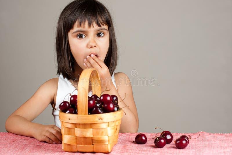 Belle petite fille mangeant des cerises image libre de droits
