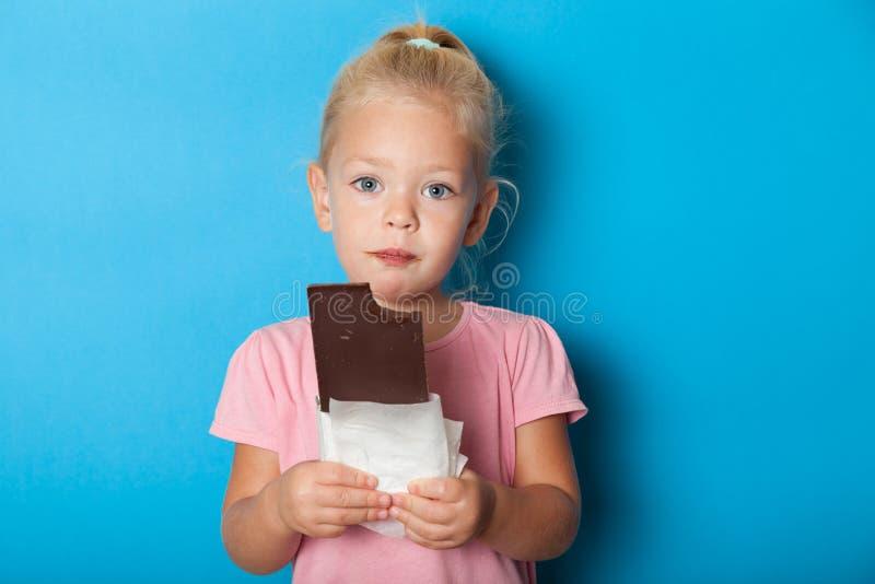 Belle petite fille mangeant du chocolat sucré Sucre, antidépresseur photo libre de droits
