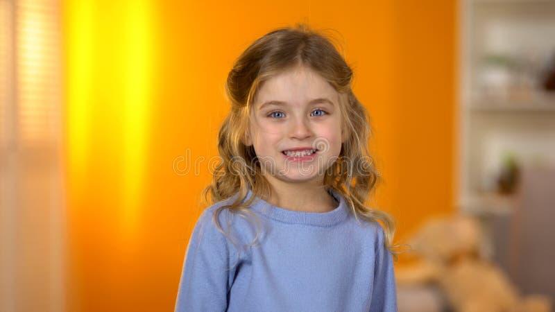 Belle petite fille montrant les dents saines ? l'art dentaire d'enfant de cam?ra et au soin oral photo stock