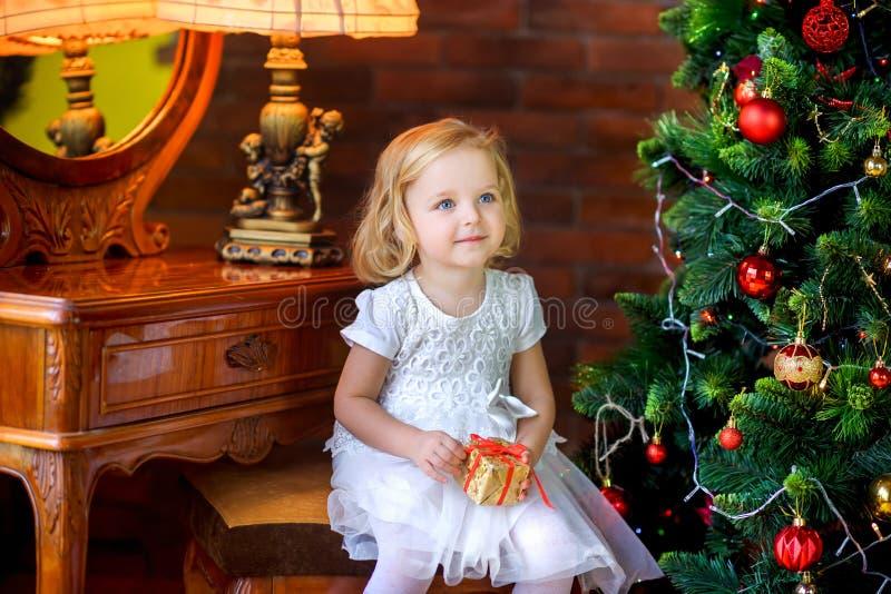 Belle petite fille près de l'arbre de Noël de fête tenant le cadeau photos libres de droits