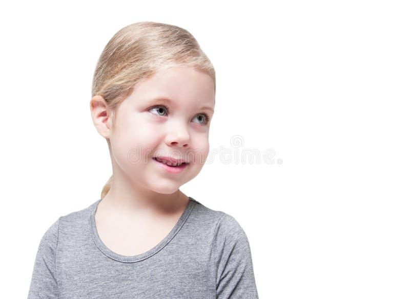 Belle petite fille regardant sur quelque chose d'isolement photos stock