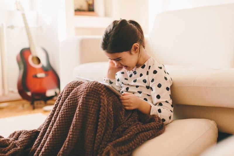 Belle petite fille s'asseyant sur le plancher avec le comprimé photographie stock libre de droits