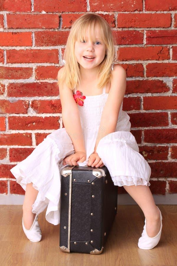 Belle petite fille s'asseyant sur un sac photo stock