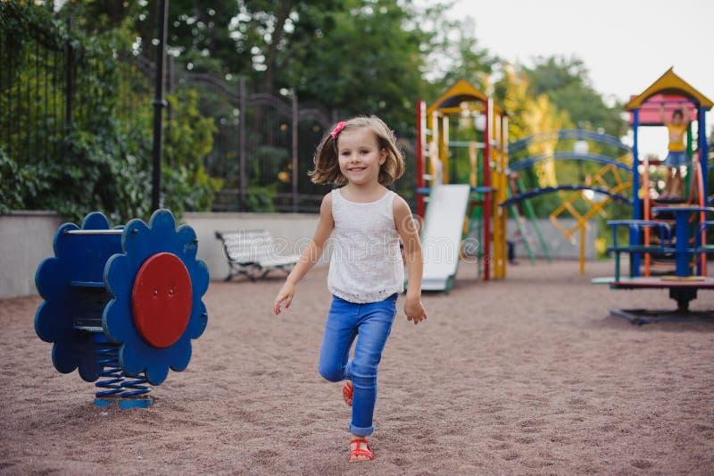 Belle petite fille sur le terrain de jeu extérieur photo stock