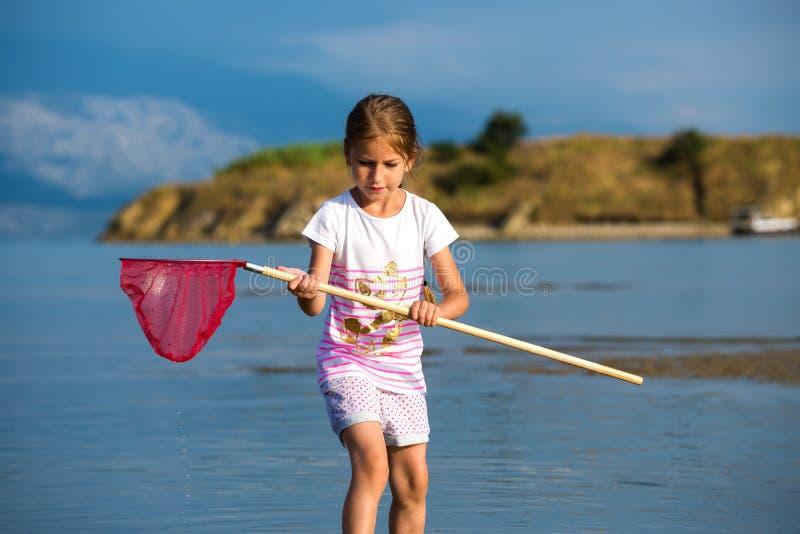 Belle petite fille sur les poissons de plage photo libre de droits