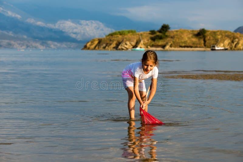 Belle petite fille sur les poissons de plage image stock