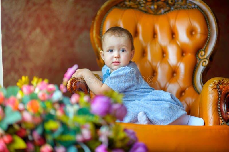 Belle petite fille sur une chaise photos stock