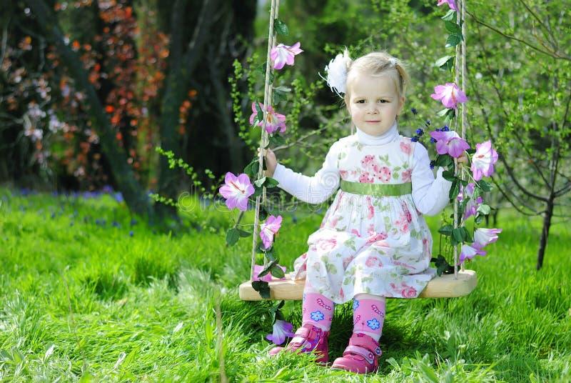 Belle petite fille sur une oscillation dans une belle robe images stock