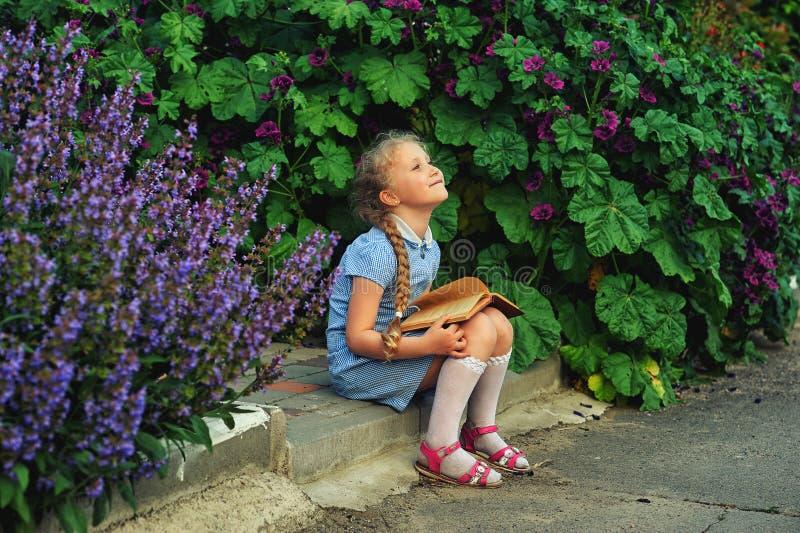 Belle petite fille tenant un livre dans la rue photos libres de droits
