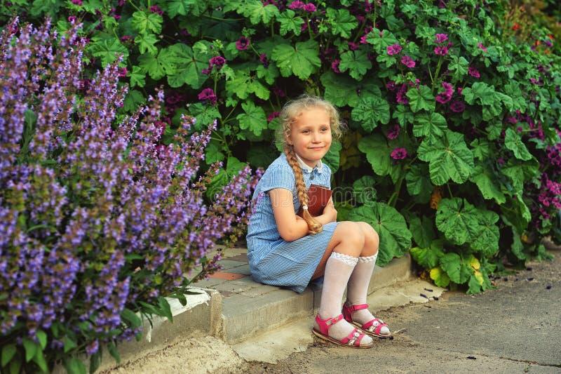 Belle petite fille tenant un livre dans la rue photographie stock