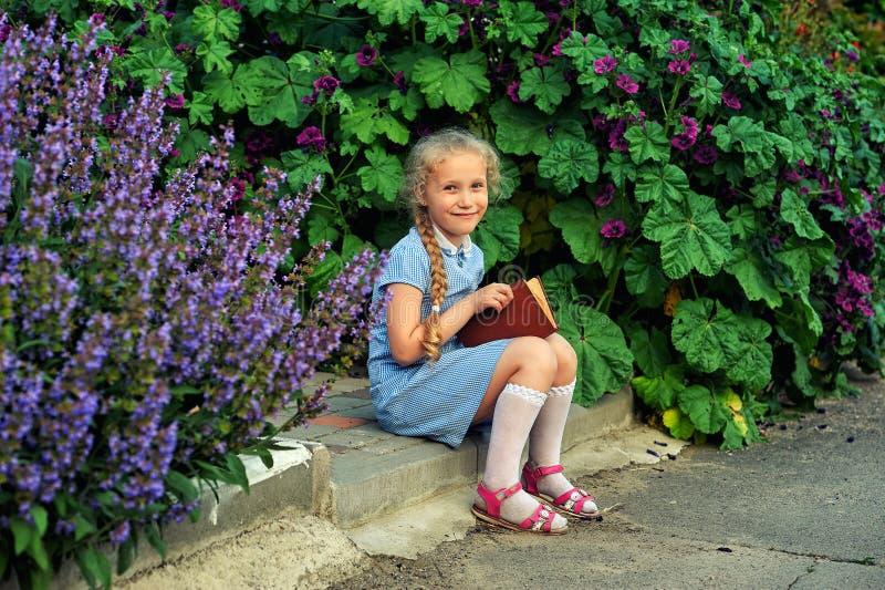 Belle petite fille tenant un livre dans la rue photo stock