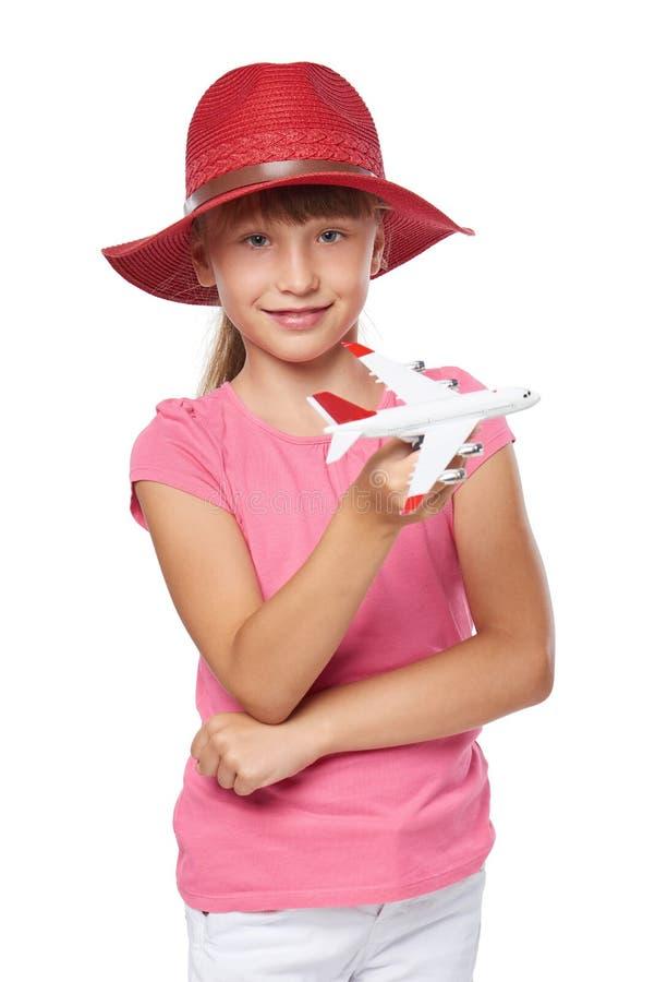 Belle petite fille utilisant le chapeau de touristes tenant le petit jouet d'avion photo stock