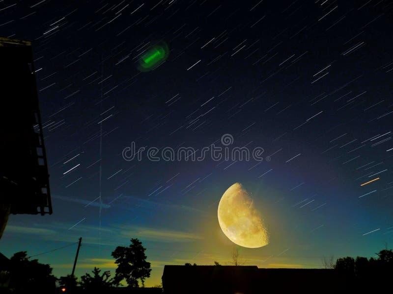 Belle photo de traînée d'étoile avec SuperMoon sur l'expression, avec des arbres, et toit de construction abandonné photo stock