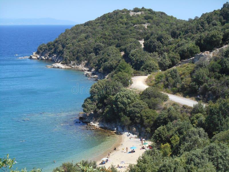 Belle photo de vue haute à la mer claire lumineuse, aux munitions de plage sablonneuse et au mountoreain avec la forêt photographie stock