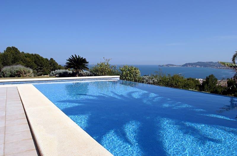 Belle piscine fraîche bleue d'infini dans une villa en Espagne ensoleillée avec des vues de mer photographie stock libre de droits