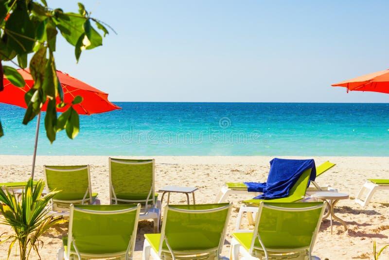 Belle plage sablonneuse tropicale avec des chaises et des parapluies de plate-forme en mer des Caraïbes de turquise chez la Jamaï images libres de droits
