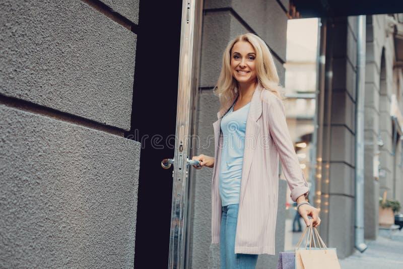 Belle porte d'ouverture blonde de femme du magasin d'habillement photos stock