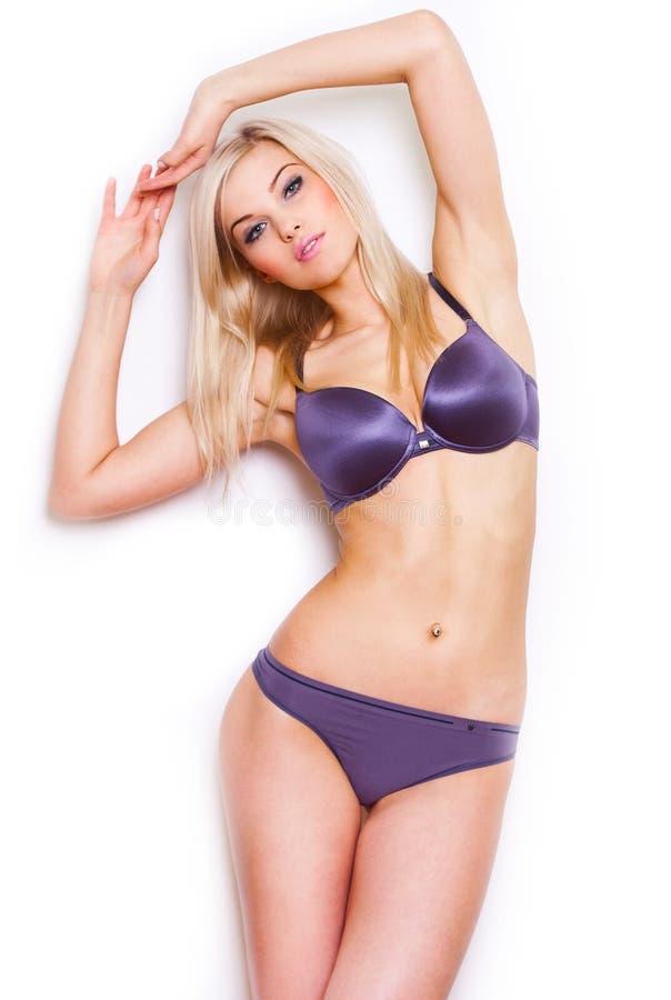 Belle pose blonde bien faite dans un bikini violet. photos stock