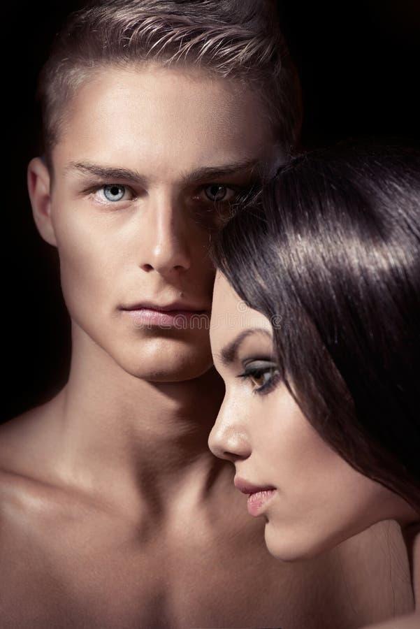 Belle pose sexy de couples d'isolement sur le fond noir images stock