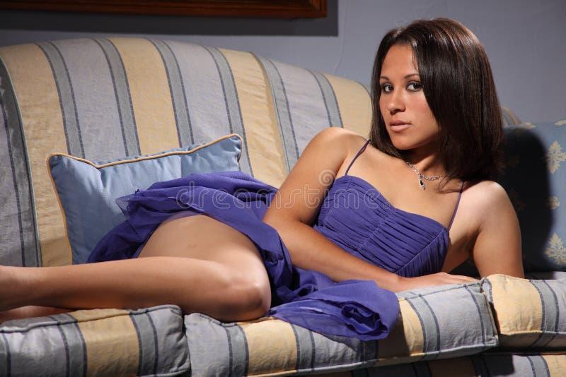 Belle pose sexy de modèle de mode se trouvant sur le sofa photo libre de droits