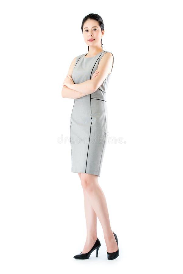 Belle position asiatique sûre de bras de croix de femme d'affaires photographie stock