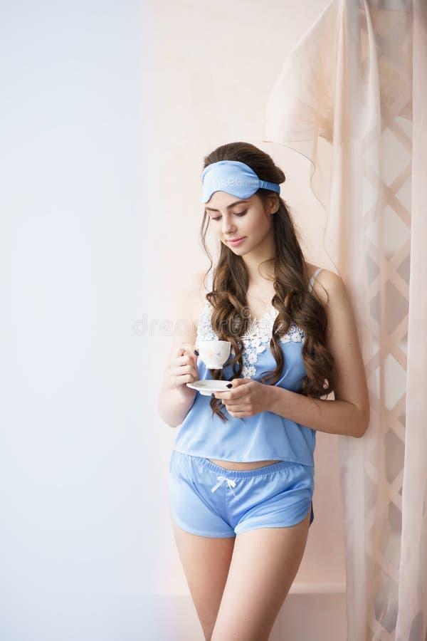 Belle position de femme près de fenêtre avec du café dans l'ensemble bleu de pyjama - camisole et shorts avec la dentelle image stock