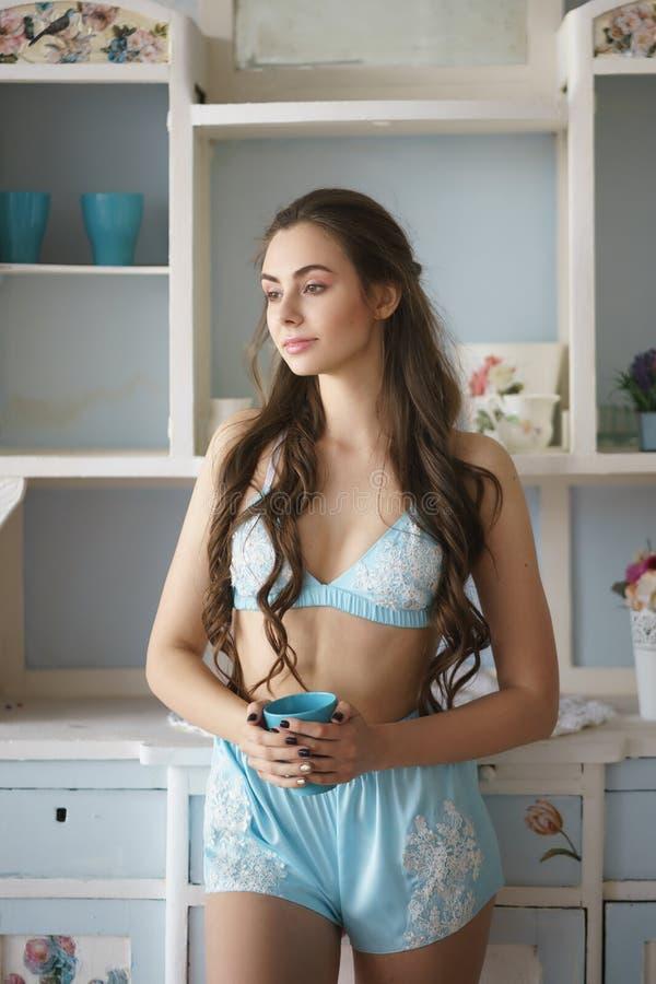 Belle position de femme près de fenêtre avec du café dans l'ensemble de pyjama de turquoise - camisole et shorts avec la dentelle photographie stock