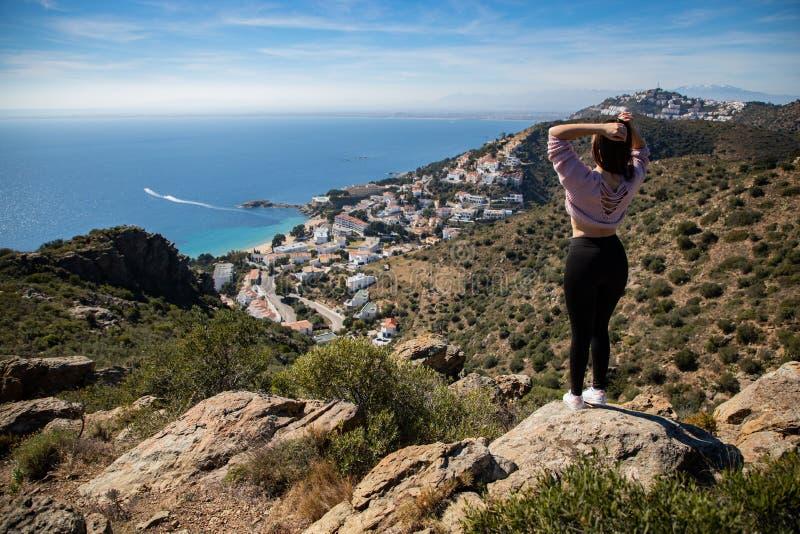 Belle position de femme sur une falaise avec la mer Méditerranée et la petite ville de côte à l'arrière-plan photographie stock