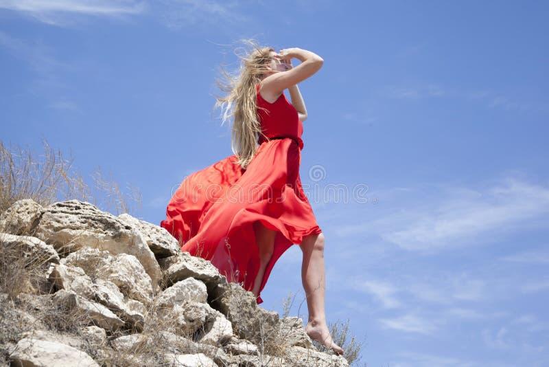 Belle position de fille au bord d'un mur en pierre Le vent développe de longs cheveux et robe photo stock