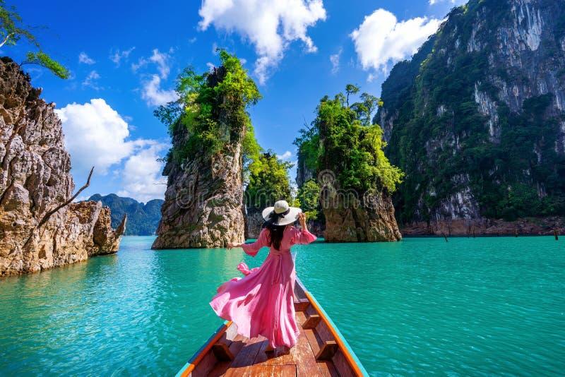 Belle position de fille sur le bateau et regard aux montagnes dans le barrage de Ratchaprapha photographie stock libre de droits