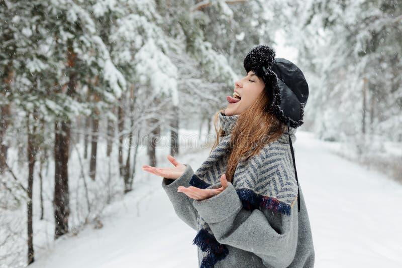 Belle position de jeune femme parmi les arbres neigeux dans la forêt d'hiver et la neige de apprécier photographie stock
