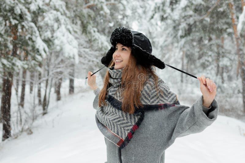 Belle position de jeune femme parmi les arbres neigeux dans la forêt d'hiver et la neige de apprécier photographie stock libre de droits